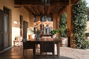 Wicker chairs around simple wooden table on roofed terrace adjoining house with walls painted apricot