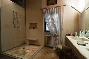 Shower with glass partition opposite masonry washstand in rustic bathroom