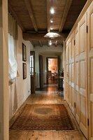 Pale, wooden custom cupboards and modern spotlights on wood-beamed ceiling in hallway