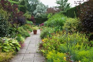 Stone-flagged garden path leading between flowering herbaceous borders in landscaped garden