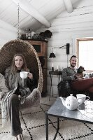 Young couple and dog in wintry living room in log cabin