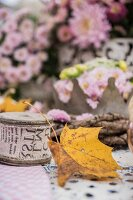 Autumnal arrangement of sycamore leaf, chrysanthemums and reel of printed ribbon