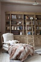 Blanket on comfortable armchair in front of bookcase with library ladder in country-house interior