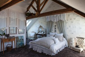 Lace-edged pillows on double bed with pelmet and curtains in romantic attic bedroom