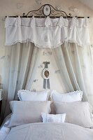 Lace pillows on romantic bed below translucent curtains and pelmet