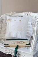 Cushion with white lace cover on antique cane chair