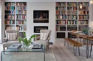 Dining area with rustic wooden furniture on delicate wire frames and armchairs in front of fireplace flanked by bookcases