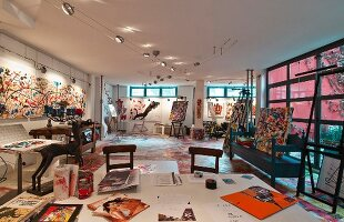 Painter's studio in loft with colourful modern paintings and pictures on wall and large desk in foreground