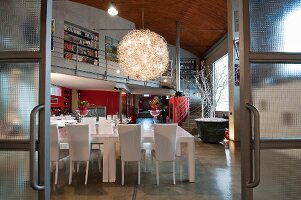 View through industrial-style glass sliding doors of white dining set below spherical chandelier in loft apartment