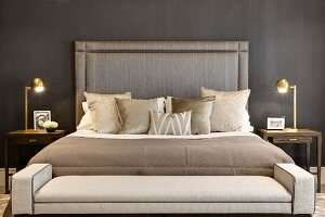 Ottoman at foot of double bed with tall headboard flanked by brass bedside lamps in elegant bedroom