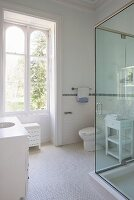 White bathroom; washstand with sink integrated in base unit, glass shower cabinet and white mosaic floor tiles