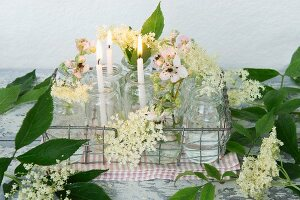 Candles, elderflowers and blackberry blossom in glasses in metal basket