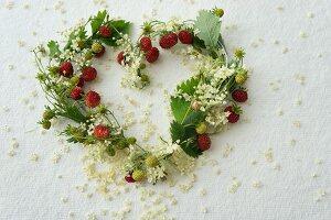 Heart-shaped wreath of wild strawberries and elderflowers
