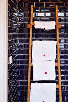 White towels on wooden ladder used as towel rail leaning against wall with dark blue subway tiles