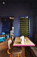 Wooden table with edge painted pink and leather-covered chairs in restaurant with dark blue walls