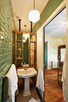 Narrow bathroom area behind sliding door with green retro tiles and view into bedroom