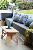 Built-in grey bench with colour-coordinated cushions and wooden stool used as coffee table on terrace