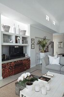 Vases and TV on fitted shelving above firewood niche and vintage accessories in seating area