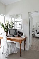 Flowers, monitor, horse ornament and table lamp on table with loose-covered chair