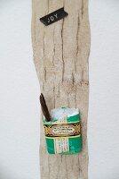 Ehemalige Seifenverpackung als Aufbewahrungsbox an Holzbrett als Pinnwand