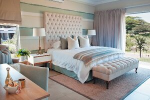 Elegant bed with button-tufted headboard and ottoman in front of open sliding door