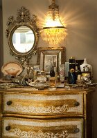Chest of drawers with gilt details and jumble of ornaments on top below crystal sconce lamp and mirror in ornate gilt frame