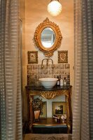 Baroque-style washstand with gilt details and white china basin below oval, gilt-framed mirror seen through open curtains in doorway
