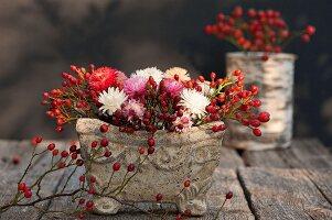 Herbstliches Blumengesteck mit Hagebutten in Steinschale auf Holztisch