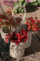 Rose hips in small wicker baskets on wooden table
