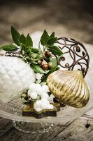 Christmas arrangement with snowberries and kermes-oak acorns on glass cake stand