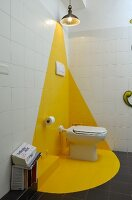 Toilet in white and yellow corner of bathroom