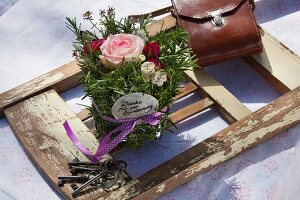 Arrangement of roses and herbs decorated with ribbon lying on detached backrest of old chair