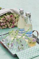 Gläser und Limonadenflaschen mit Schnappverschluss im Vintage Stil auf schlichtem Metall Tablett, im Hintergrund üppiger Rosenstrauss