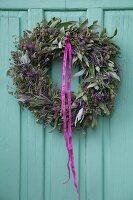 Kräuterkranz aus Lavendel und Salbei an türkisfarbener Holztür aufgehängt