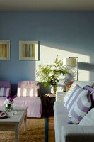 Pastel sofa and easy chairs with striped scatter cushions in living room with pale blue wall
