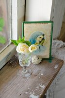 White flowers in crystal glass and Madonna icon on vintage windowsill