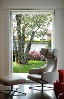 Designer-Relaxsessel mit Fußhocker von Antonio Citterio vor Fenster mit Gartenblick