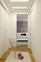 White, feminine dressing room with fitted wardrobes, elegant metal chair and view into simple bedroom