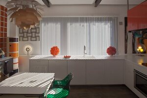 Dining set below classic pendant lamp, modern white kitchen counter below window with vertical louvre blinds