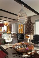 Retro black and white leather armchairs around round coffee table and designer lamp in front of zebra skin on wall