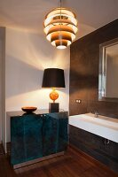 Table lamp on elegant sideboard, sink and retro pendant lamp in designer bathroom