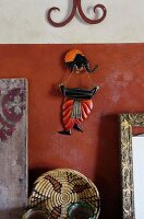 Far-Eastern wall decoration with elephant figurine above hand-crafted raffia basket against red-brown wall