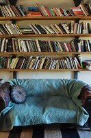 Vintage sofa with turquoise blanket below bookshelves