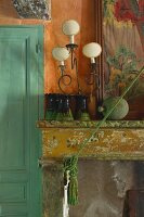 Collection of vases and vintage-style table lamp on mantelpiece with peeling paint
