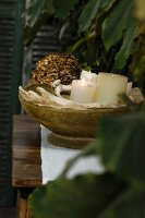 White pillar candles in vintage stone bowl
