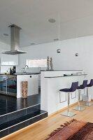 Moderne, gepolsterte Barhocker vor minimalistischer Frühstückstheke in offener Designerküche