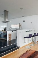 Modern, upholstered bar stools at minimalist breakfast bar in open-plan designer kitchen