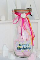 Pink, heart-shaped mashmallows in a glass bottle as a gift