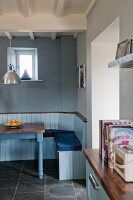 Rustic dining area in shades of blue with built-in bench and table with walnut top