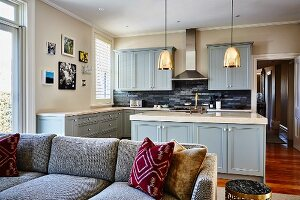View past sofa into open-plan country-house-style kitchen with grey-blue fronts
